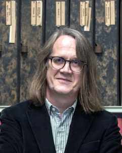 a photograph of Paul Taylor standing in front of shelves supporting filing boxes. The image is cut off at his chest. He is looking straight at the camera, and is smiling. He is clean-shaven and has long blond hair which rests on his shoulders. He is wearing glasses, a green and white striped shirt and a blue corduroy jacket. Behind him there are two rows of tall filing boxes, one red, the other mottled black and brown. Hand-written and typed labels on each box refer to their contents. The boxes contain photographs of works of art, and form part of the Photographic Collection of the Warburg Institute, where Paul works.