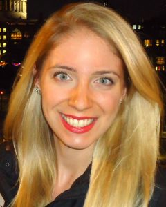 color photograph of a blonde woman with blue eyes wearing a dark shirt and smiling at the camera.