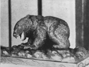 This is a black and white image of a sculpture that looks like a large animal, likely a bear on its four legs with its mouth open.