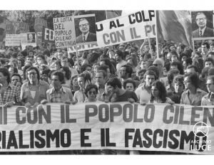 "This is a black and white photograph of a group of protestors holding a banner that reads ""[With] the Chilean people, [against] imperialism and fascism."""