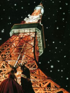 """A couple standing in front of the Tokyo Tower at night. The text above reads """"pizzicato five 24 Decembre ep""""."""