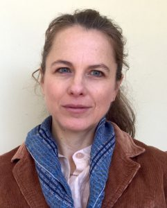 Photograph portrait of a woman standing against a white wall with her brown hair pulled back from her face. She wears a blue scarf and a brown tweed jacket.