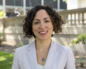 Color photograph portrait of a smiling woman with curly brown hair standing outside a university building at UW-Madison wearing a white shirt and jacket and silver jewelry