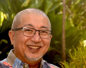 Color photograph of a smiling man wearing glasses and an aloha shirt standing in front of tropical greenery