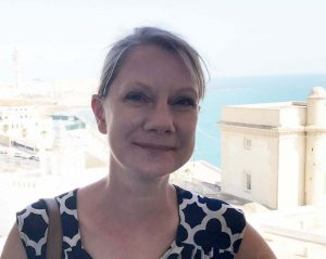 Photograph of Tanya Tiffany (white woman wearing a black and white dress with her hair pulled back) standing outdoors in Cadiz, Spain in front of a blue ocean.