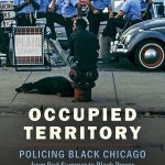 Book cover of Occupied Territory. It is a photograph. In the foreground there is a man sitting on a fire-hydrant with a long laying on the sidewalk. In the background there is a group of about seven police officers perched on parked cars and chatting.