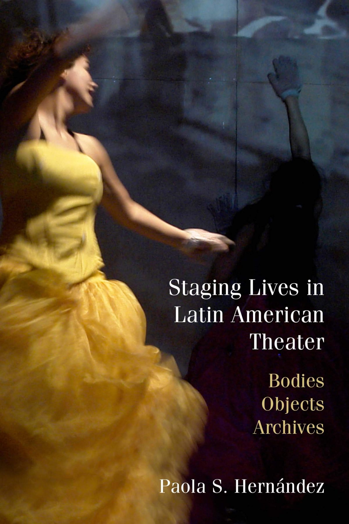 The image is over the cover of the book of Staging Lives in Latin American Theater. The background is dark gray with the image of a woman in a yellow dress in moment. Perhaps dancing. Her face is turned and is not fully visible to the viewer.