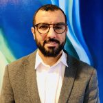 Image description: A bio photo for Baligh Ben Taleb. He is wearing glasses. He has on a tweed jacket with a white shirt underneath.