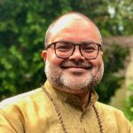 Image Description: This is a photo of B. Venkat Mani. He is looking at the camera and smiling. Behind his is green foliage.