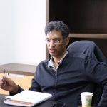 Image Description:Viren Murthy, wearing a black sweater, seated at a black desk looking at the camera from an angle. He has a pen in his hand and an open notebook in front of him.