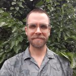 Image description: This is an image of Andrew Thomas. He is standing outside with trees and foliage in the background. He is wearing clear frame glasses and a gray shirt.